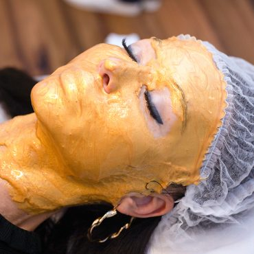 Young woman with facial golden mask in a beauty salon.