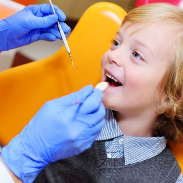 portrait of a smiling child with blonde curly hair on examination in a dental chair. Pediatric dentistry